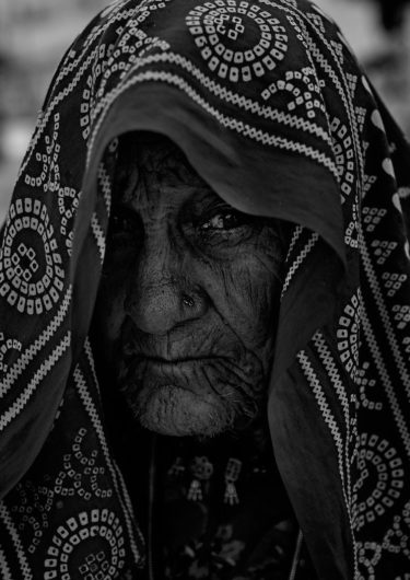 Black and White Photography with the title 'India 7'. Portrait of an Indian Woman with a scarf over her head.