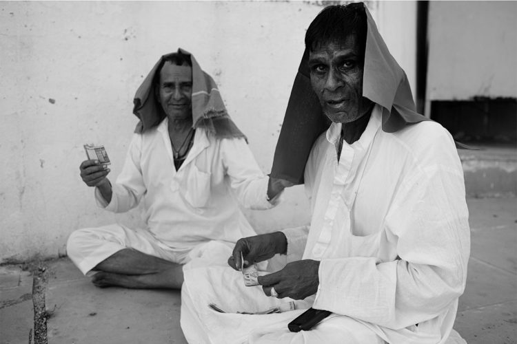 Black and White photography with the title 'India 24'. Portrait of two traditionally dressed Indian men sitting on the floor.