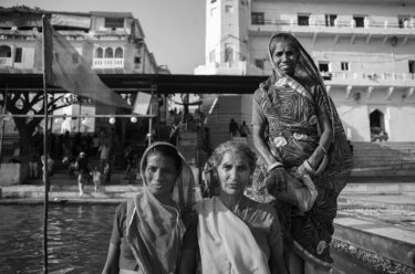Black and white photography with the title 'India 25'. Portrait of three traditionally dressed Indian women floating on a boat.
